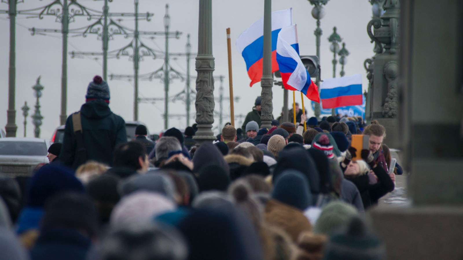 A large crowd of people carrying Russian flags cross a bridge