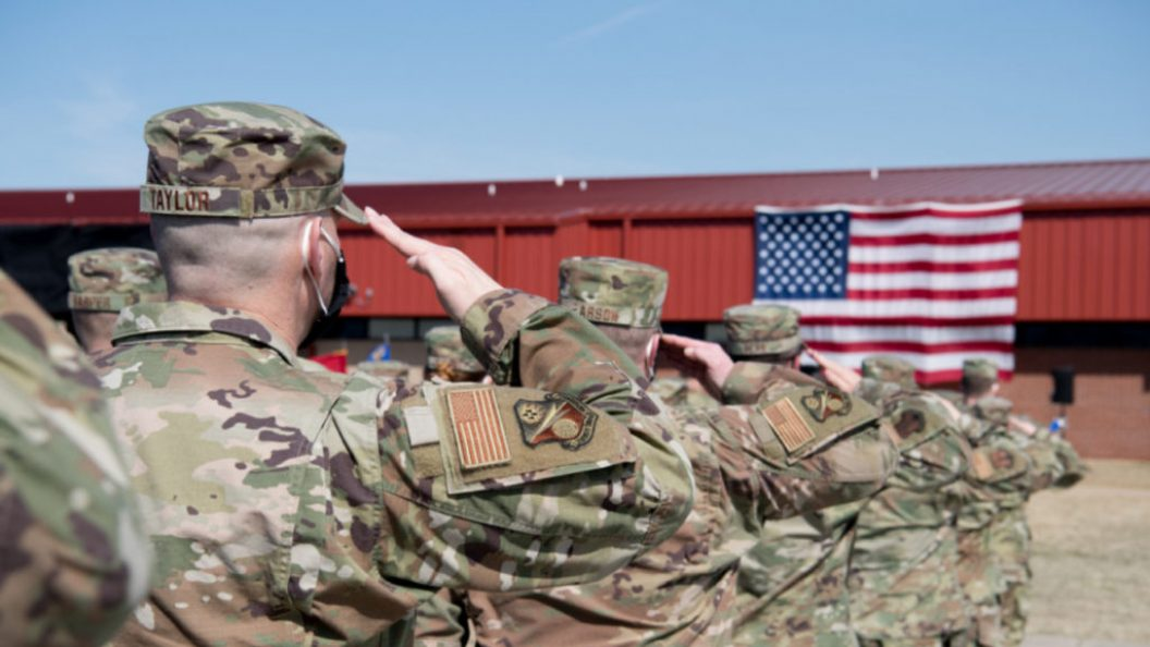 Members of the military in camouflage uniform salute the U.S. flag