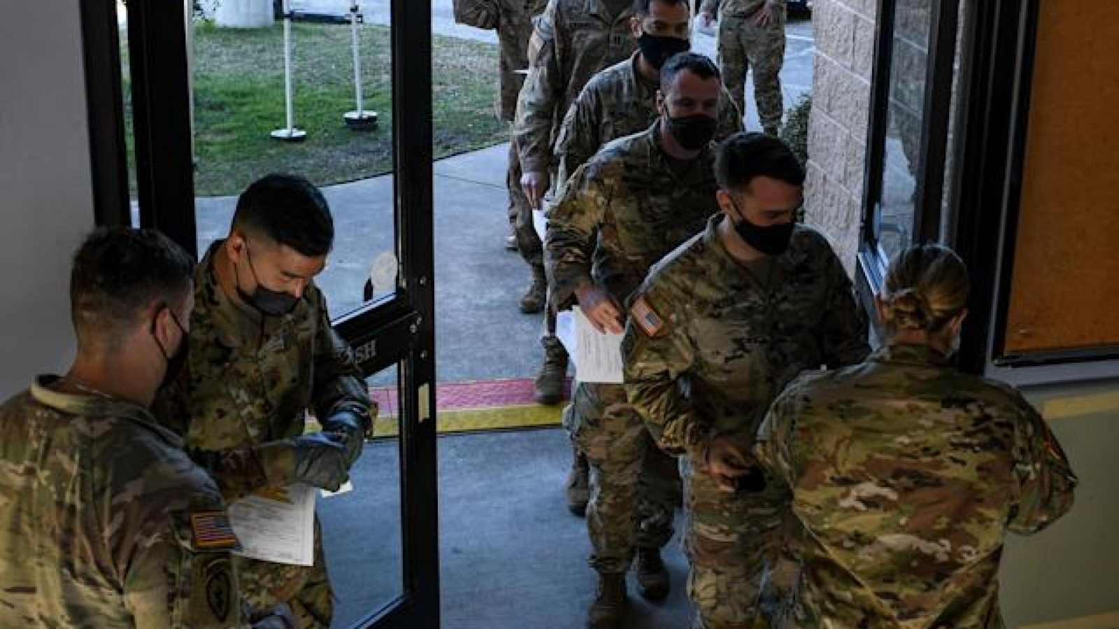 Members of the U.S. military in green camouflage uniforms line up through a door