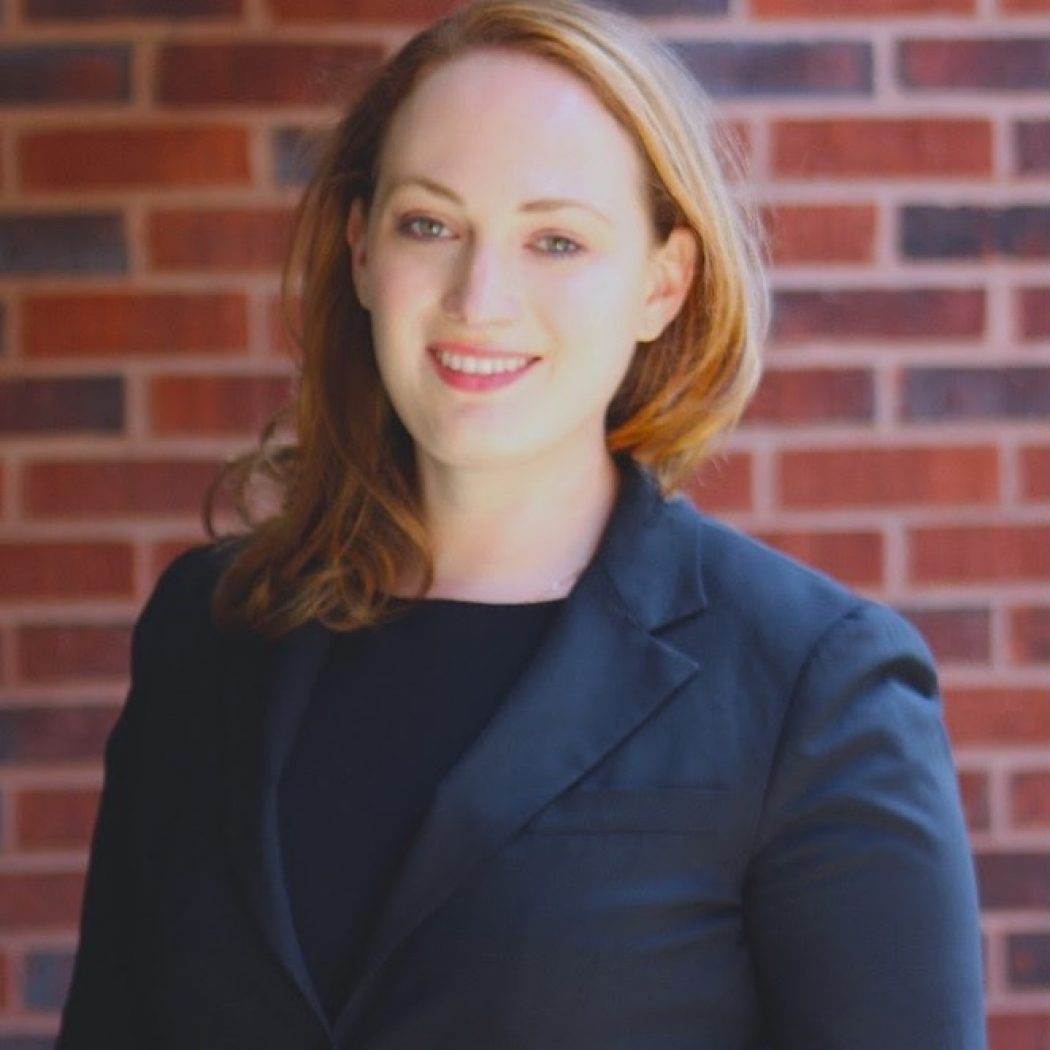 A white woman wearing a black top and blazer is photographed in front of a brick wall