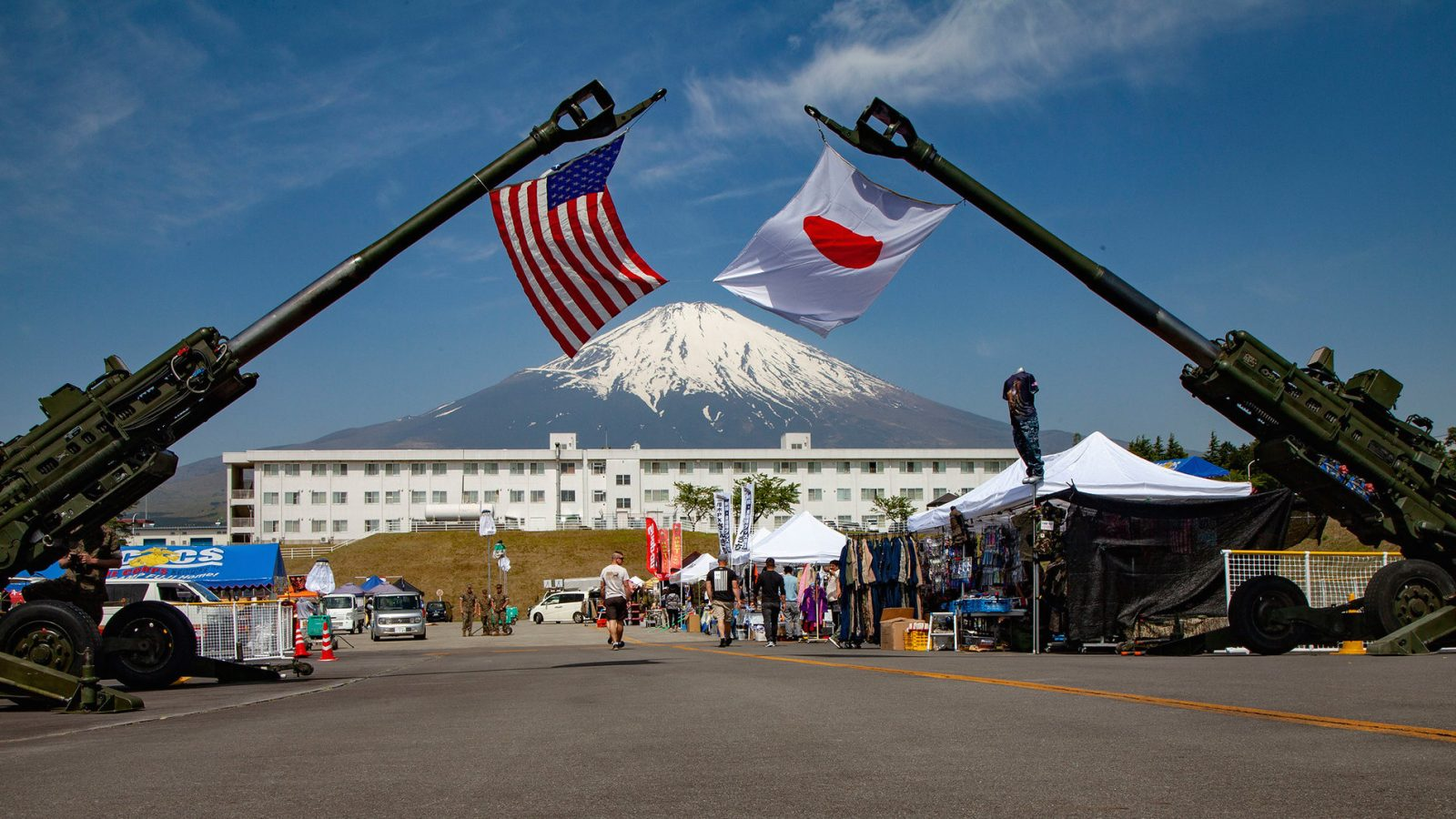 Two artillery weapons hoist the Japanese and U.S. flags with Mount Fuji in the background