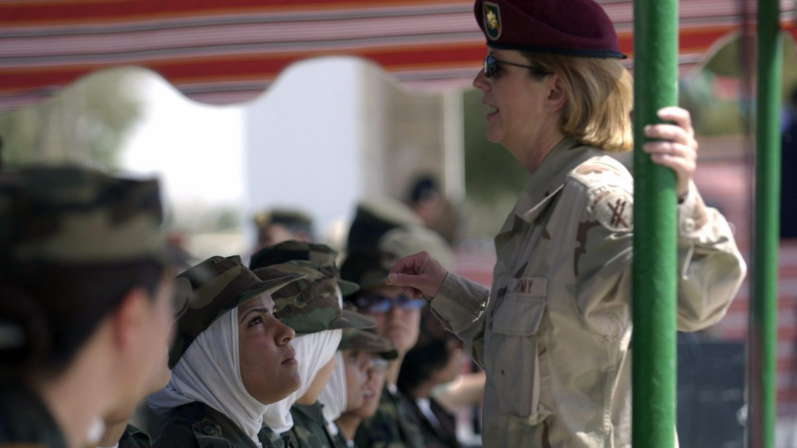 A woman in a green U.S. Army uniform speaks to a group of Iraqi army women