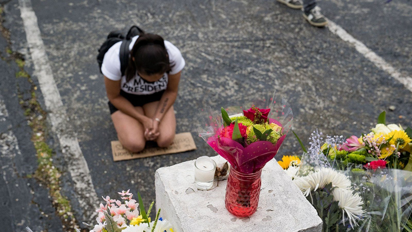 A woman kneels on a concrete parking lot in front of bouquets of flowers