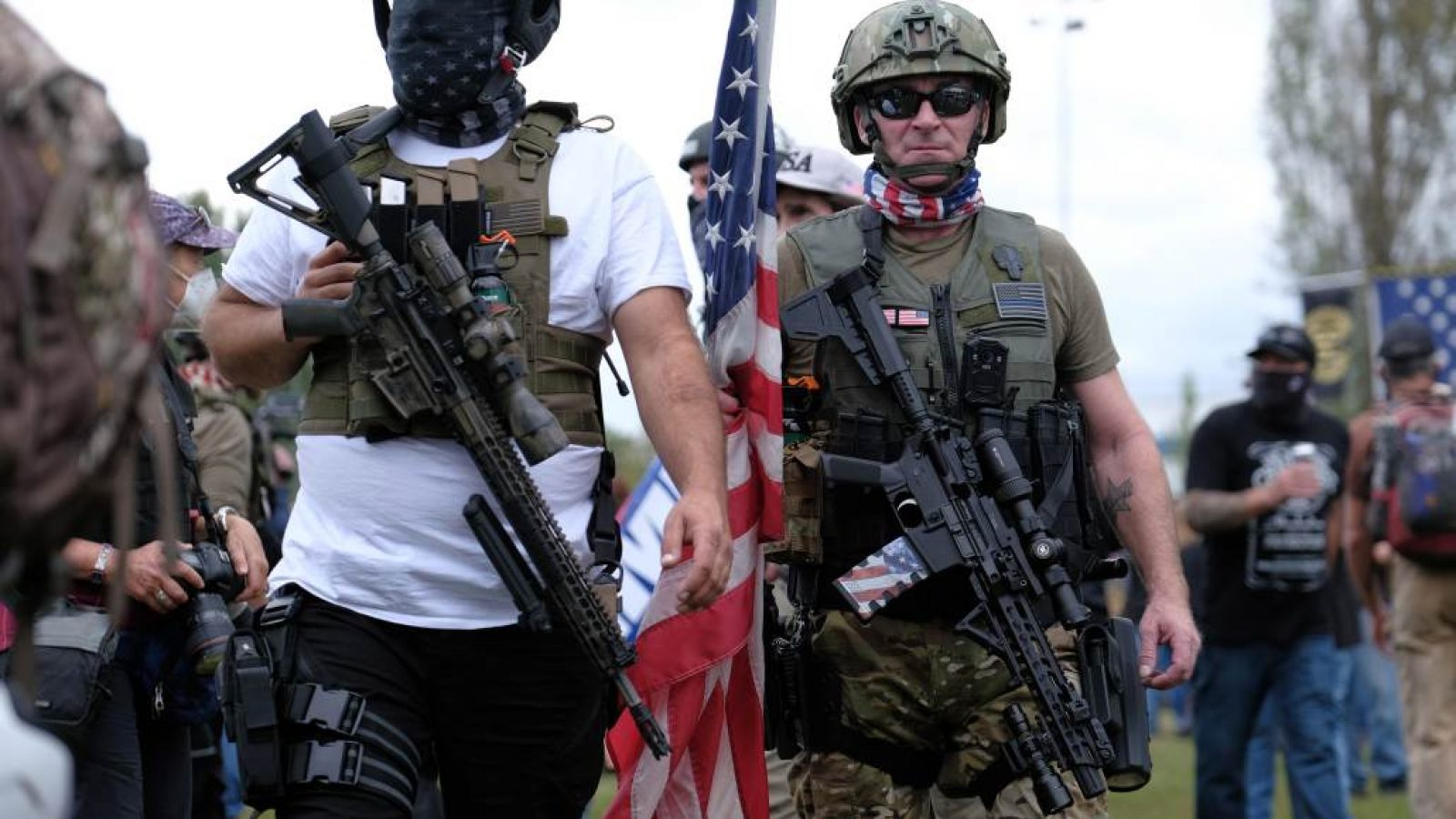 Men wearing bulletproof vests carry rifles and a large American flag