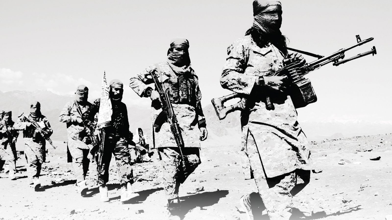 A black and white photograph of Taliban fighters carrying weapons and crossing a rocky terrain