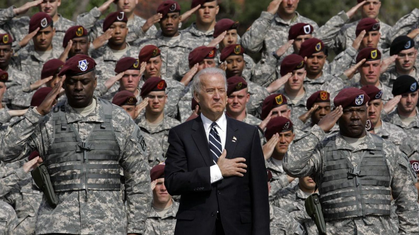 Joe Biden in a suit puts his hand over his heart and and Lloyd Austin in a green camouflage uniform salutes in the foreground, with soldiers in green camouflage saluting behind them