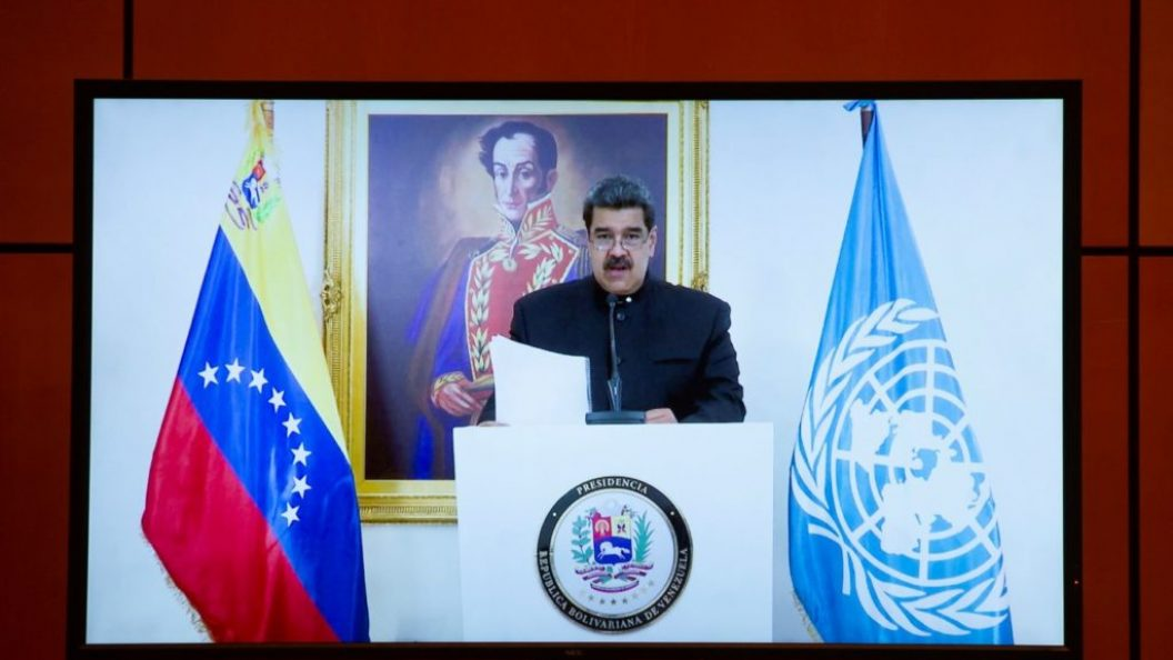 Nicolas Maduro is flanked by a Venezuelan and UN flag as he stands at a podium for a speech