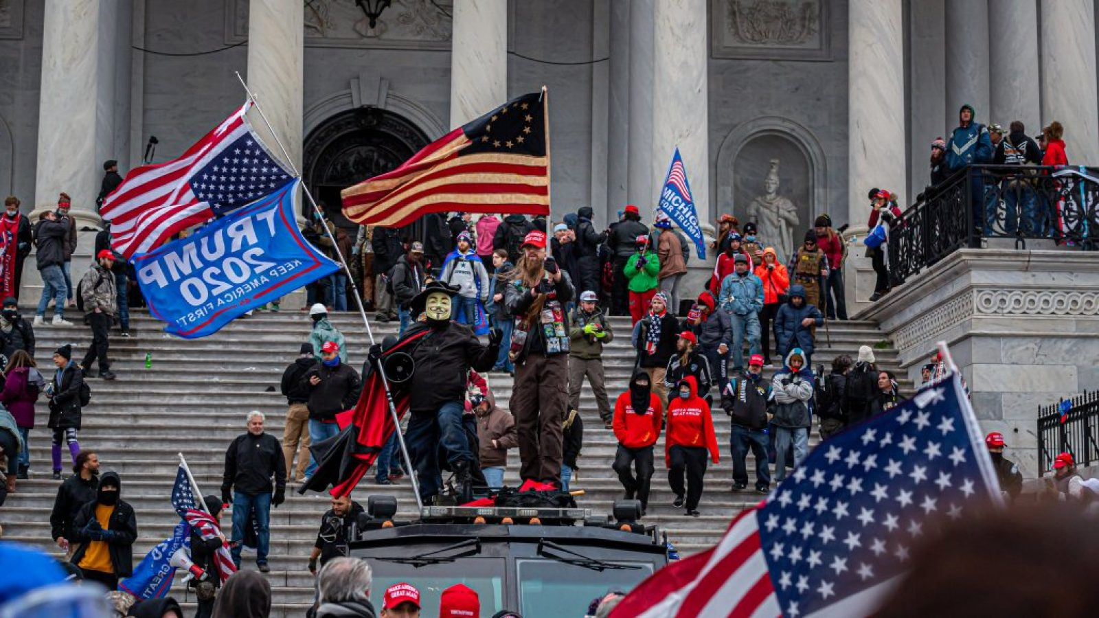 A large crowd of rioters carrying American flags and Trump 2020 flags stand on the U.S. Capitol steps