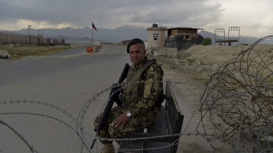 An Afghan soldier in green camouflage holds a black rifle as he sits by a road behind barbed wire