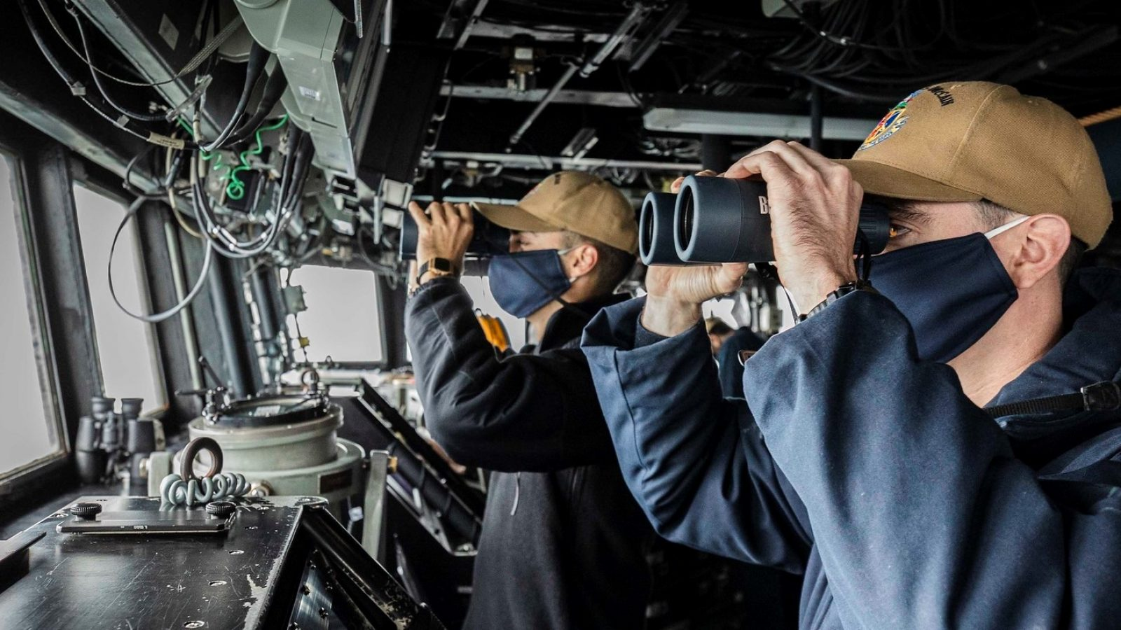 Two men peer through binoculars in the pilot house of a destroyer
